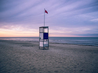 Wall Mural - Lifeguard stand on a deserted beach at sunset.