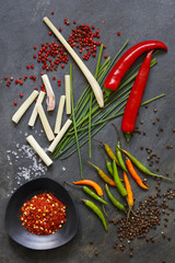 Ground dried chilli peppers with fresh peppers, lemon grass and chives on slate background