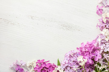Tiny flowers of Lilac on an old wooden background.  Floral border.