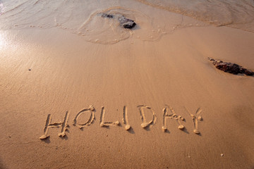 """Holiday"" written in the sand on the beach in the background"