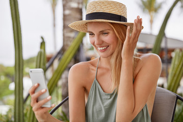 Happy European woman in straw hat glad to recieve text message on smart phone, types feedback, has charming smile, spends leisure time at cafe. Pretty young female chats in social networks on cellular