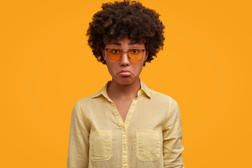 Portrait of discontent African American female curves lower lip as being abused by someone, displeased with results of her project work, doesn`t recieve praisement, isolated on yellow background