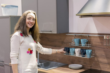Happy young woman in a modern new kitchen. Happy young woman with long hair