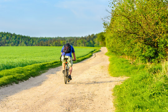 A cyclist riding a dusty road at sunset. Cycling on holiday in the Czech Republic.
