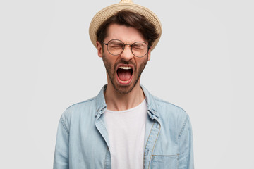 People, aggression, discontent concept. Photo of bearded desperate male in countryside clothes, keeps mouth opened, screams loudly, expresses negative emotions, isolated over white background.