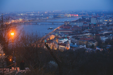 Beautuful super-wide angle aerial night view of Budapest, Hungary, with Danube river, Parliament building and scenery beyond the city, seen from observation point of Gellert Hill
