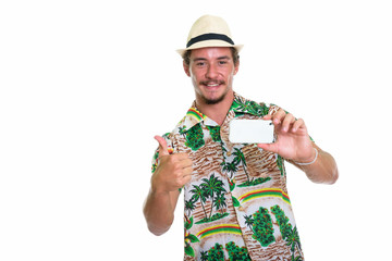Studio shot of young happy tourist man smiling while taking pict