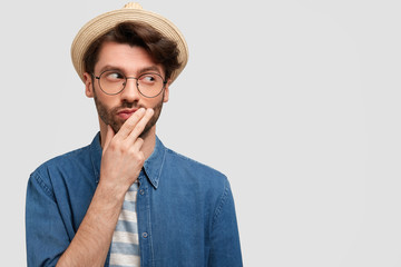 Pensive unshaven male keeps hand on chin, wears casual denim shirt and elegant hat, looks away, has thoughtful expression, isolated on white background with copy space for your promotional text