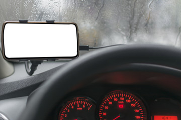 Driving a car with smartphone in holder, rainy day