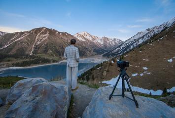 photographer takes a sunset in the mountains, a mountain lake, Kazakhstan, Almaty