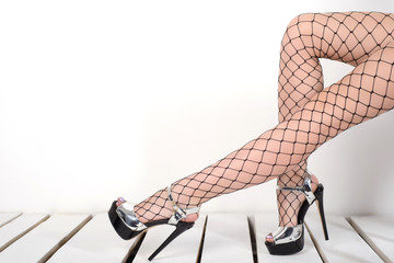 Seductive woman's legs wearing fishnet stockings and high heels silver shoes