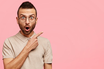 Portrait of amazed attractive male has trendy haircut, wears casual t shirt and glasses, points with fore finger at blank copy space, stands against pink background. People, style and emotions concept