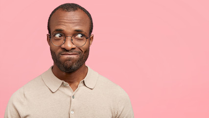 Photo of hesitant dark skinned male manager curves lips, looks aside, notices beautiful female aside, stands against pink background with copy space. Unshaven young African American guy indoor