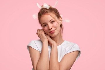Photo of delighted female with attractive look, has healthy soft skin, feathers in head, being pleased after unforgettable night with lover, looks happily directly at camera, isolated on pink wall