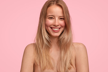 People, natural beauty and positive emotions concept. Pleased young female with long hair, poses nude against pink background, smiles joyfully as being photographed for popular fashion magazine