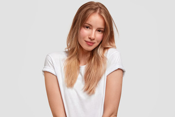 Horizontal shot of good looking Caucasian female model wears white t shirt in one tone with background, looks delightfully at camera, being satisfied with new purchase. Monochrome and trend.