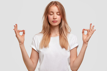 Photo of relaxed beautiful female keeps eyes shut, wears casual white t shirt, makes yoga gesture, isolated over studio background. People, meditation, wellness, relaxation and lifestyle concept