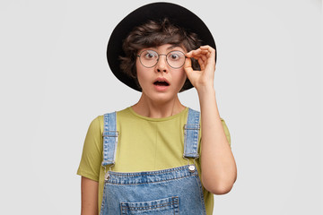 Pleasant looking amazed woman stares at camera with bated breath, recieves shocking news, wears spectacles, jean overalls and hat, looks scrupulously in front, tries to notice something little