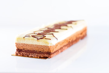 Delicious chocolate cake on white background, closeup. Three layers of different chocolate filling.TriColad cake-Triple color  Mousse. Selective focus.