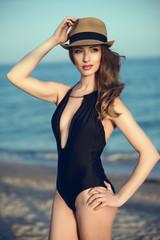 Portrait of beautiful glamour model standing at the seaside wearing stylish straw panama with black hat band and trendy one piece halter neck swimsuit with plunging neckline