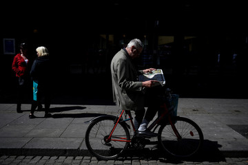 A man stops on his bicycle to read a newspaper in the city centre of Dublin