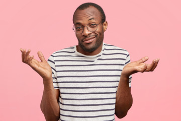 Clueless cheerful dark skinned male shrugs shoulders with hesitation, feels doubtful, wears striped t shirt, isolated on pink background. African American man expresses disbelief, models in studio