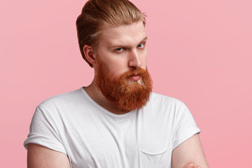 Close up portrait of serious male with trendy haircut and ginger beard, wears casual t shirt, looks confidently at camera, has strict expression, perfect skin poses against pink studio background