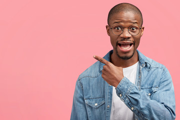 Handsome amazed African American bald man with bristle, wears fashionable denim shirt, indicates at blank copy space on pink background, advertises something. People, advertisement, emotions