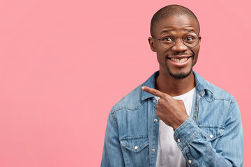 Satisfied dark skinned male looks with content glad expression, has healthy skin, stubble, points with fore finger aside at blank copy space, demonstrates place for your advertisement or text