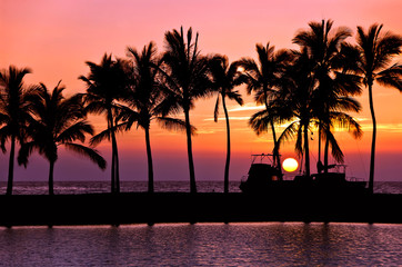 Setting sun with palm tree and boat silhouettes at Anaehoomalu Bay, Big Island, Hawaii