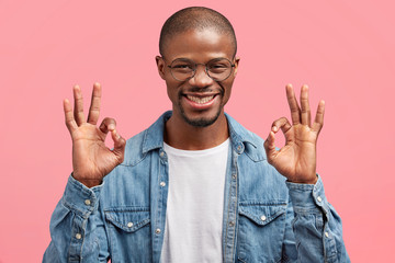 Successful male manager with dark healthy skin, makes ok sign and looks happily, rejoices well done project, wears denim shirt, poses against pink background. People and body language concept