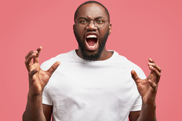 People, negative emotions and feelings concept. Annoyed black African American male gestures angrily, has quarrel with enemy, yells loudly, keeps mouth wide opened, frowns face in dissatisfaction