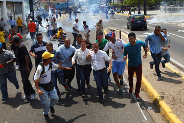 Juan Pablo Guanipa, elected governor of Zulia state, runs away from tear gas during a rally with supporters in Maracaibo