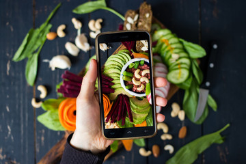 Phone photography of food. Woman hands take photo of lunch with smartphone for social media. Buddha bowl with fresh vegetables. Raw vegan vegetarian healthy dinner