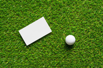 White paper background and golf ball on green grass of golf course background.