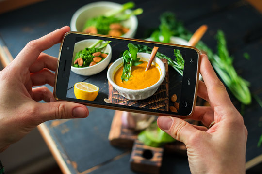 Phone photography of food. Woman hands take photo of lunch with smartphone for social media. Pumpkin soup. Raw vegan vegetarian healthy dinner