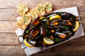 Copper pot of gourmet mussels with lemon, parsley and garlic served on a bread. horizontal top view