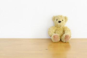 brown teddy bear on wood