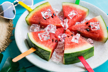 Watermelon slice popsicles with colorful stick on wooden background, Summer fruits