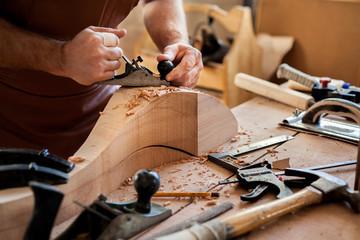 Joiner Makes Cabriole Leg for Vintage Table. Carpenter works with a planer in a workshop