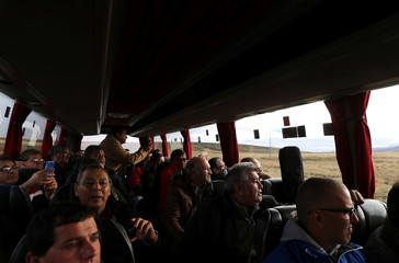 Argentine Falklands War veterans from the Argentine province of Corrientes take photos and look out the bus' windows after arriving at the Falkland Islands near Port Stanley