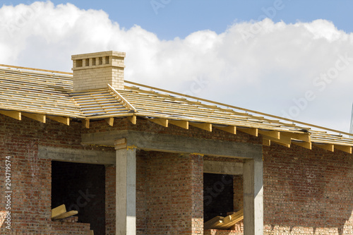 Close-up detail of wooden roof of new brick house with two white