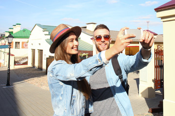 Happy couple of tourists taking selfie in old city.