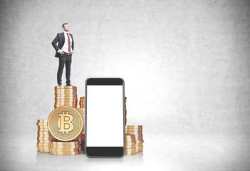 Businessman on bitcoin stacks, smartphone screen