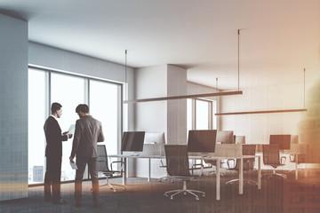 Businessmen talking in white open space office
