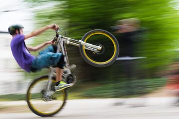 Sportlicher Radfahrer mit angehobenem Vorderrad in Bewegungsunschärfe