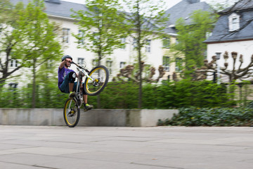 Jugendlicher in der Stadt auf dem Mountainbike in Bewegungsunschärfe