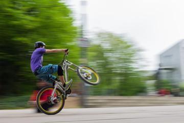 Jugendlicher Mountainbike-Fahrer mit angehobenem Vorderrad in der Fußgängerzone