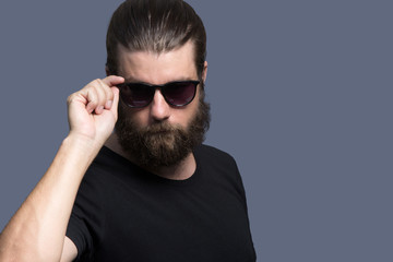 Portrait of cool serious man wearing sun glasses isolated on grey