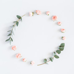 Flowers composition. Wreath made of rose flowers, eucalyptus branches on pastel gray background. Flat lay, top view, copy space, square
